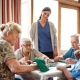 Group of women playing scrabble while caregiver observes