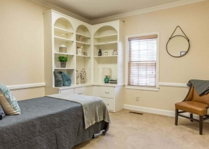 bedroom with twin bed, bookshelf and padded chair